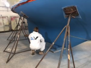 Blue antifouling completed on Puffin's bottom (with the proper logo on Glenn's back)